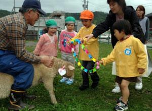 子羊に手づくりの首飾りをプレゼントする園児たち